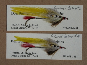 "A pair of Colonel Bates streamers. Oddly enough, and I don't like to complain, but the person for whom this fly was named had two components incorrectly labeled in his own book.  Joseph D. Bates ""Streamer Fly Tying and Fishing."" Subsequent evidence - numerous Carrie Stevens original Colonel Bates streamers, including the Captain Bates and Major Bates, show the tail to be red hackle fibers. This makes sense, since not one  of the 100-plus streamer flies she originated have sections of duck quill for tails. And the shoulders on the Colonel Bates are and always were gray mallard, not teal."